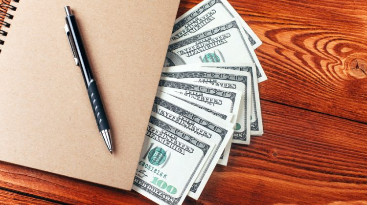 Brown notebook with dollars and pen lying on wooden table with place for text