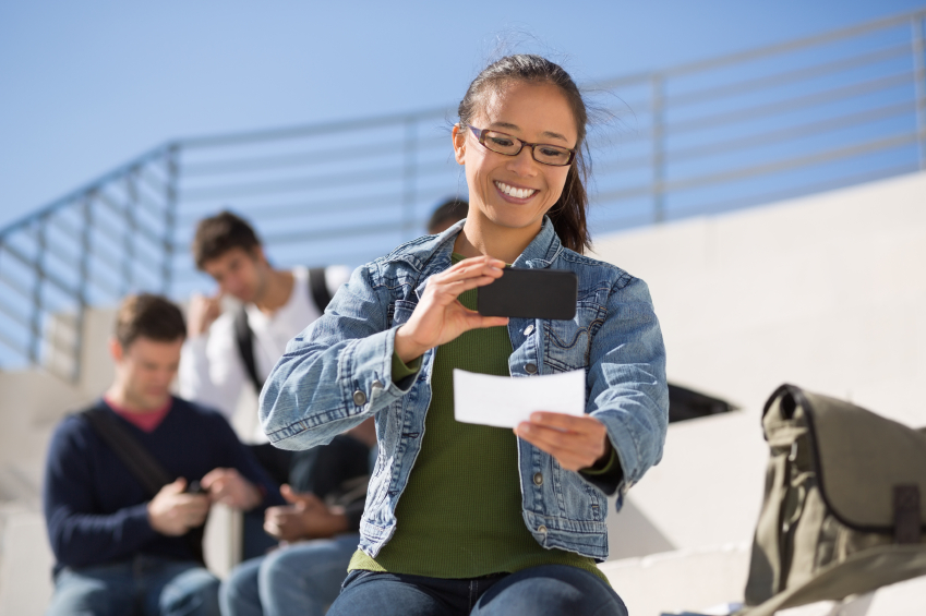 Happy young female student depositing check through mobile phone