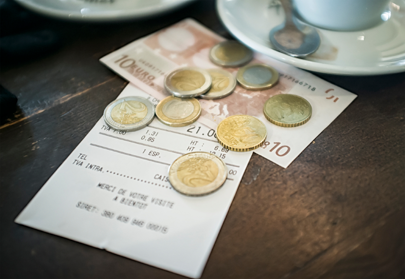 A bill with payment in Euros on the table of a cafe.  Please note shallow depth of field.