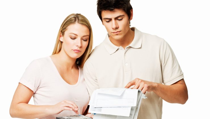 Young couple look through and calculate their bills. Square shot. Isolated on white.