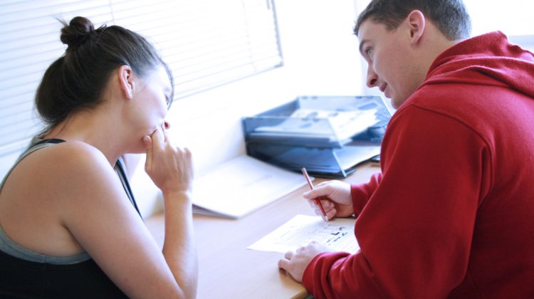 Personal_trainer_assessing_a_client's_goals_and_needs_as_they_write_a_fitness_programme