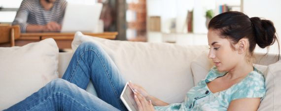 Shot of an attractive young woman using her digital tablet while reclining on the sofa at home