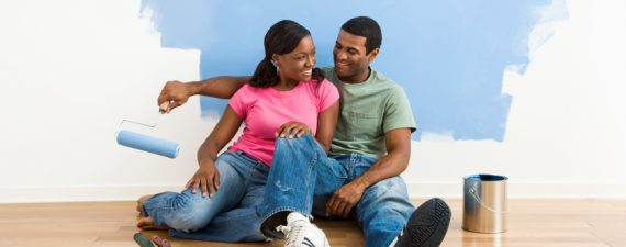 African American couple relaxing together next to half-painted wall and painting supplies.