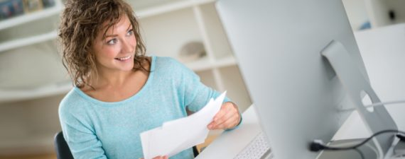 Young woman paying bills online using her desktop - home finances concepts