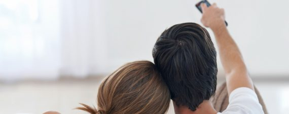 Rear view shot of a young couple watching TV together