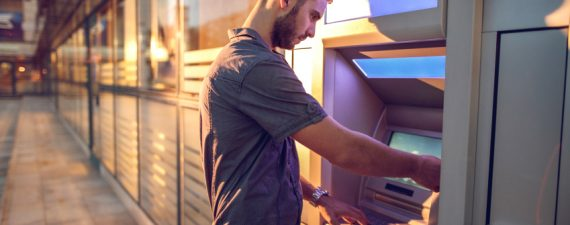 Businessman withdrawing cash from a bank's ATM.