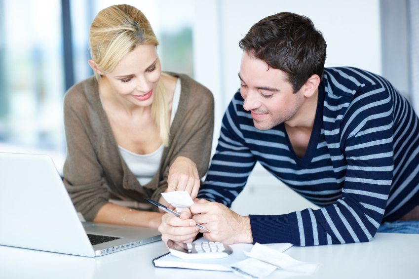 Young couple at home working out their monthly budget with calculator and receipts