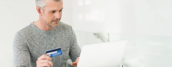 Adult man shopping online at home using a laptop computer