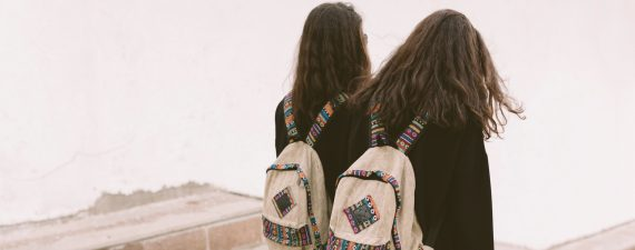 students twins with backpacks walking