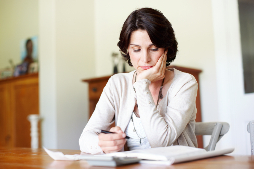 A mature woman busy budgeting