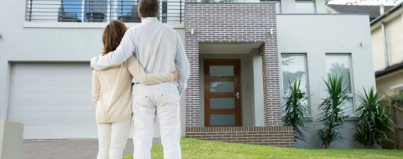 Mature couple looking at a house. Rear view
