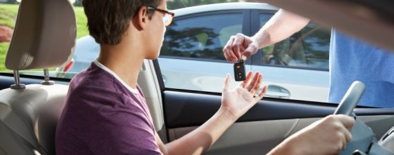 Cropped view of teenage driver taking car keys from father.  Focus on key.