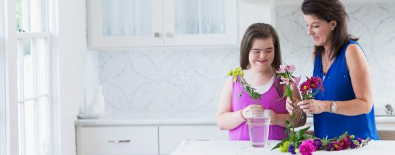 A teenage girl with downs syndrome arranging flowers in a vase with her mother. They are standing next to each other with the vase on a table in front of the girl. They are holding flowers to place in the vase, and more flowers are laying on the table.