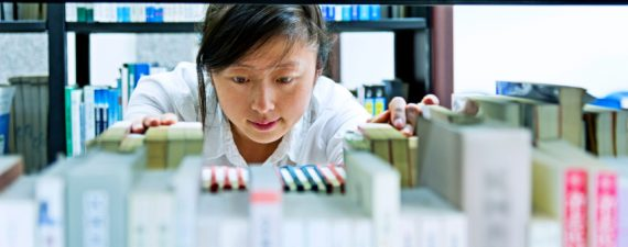 Asian young woman choosing book in library