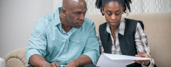 A husband and wife are sitting in their home looking over their finances and are working on their retirement plan.